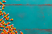 Pile of Halloween candy corn on rustic wood background with copy space.