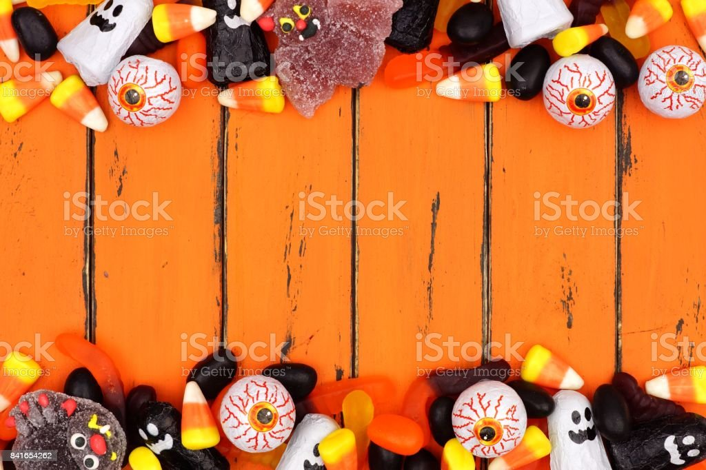 Halloween candy double border over old orange wood stock photo