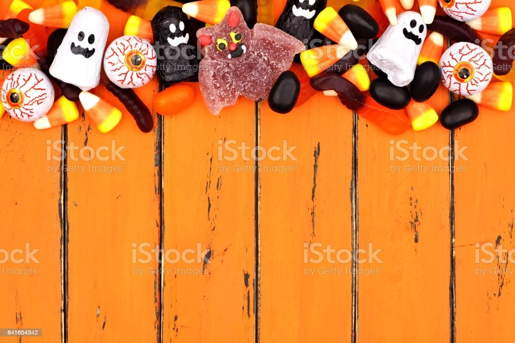 Halloween candy top border over old orange wood stock photo