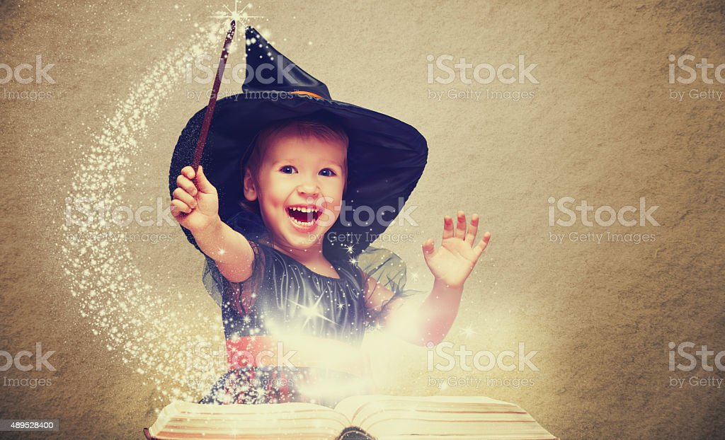 Halloween. cheerful little witch with a magic wand and glowing stock photo