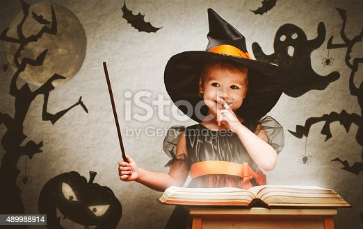 Halloween. cheerful little witch with a magic wand and the book conjure and laughs.