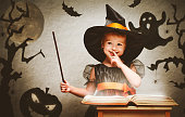 istock Halloween. cheerful little witch with magic wand and book conjur 489988914