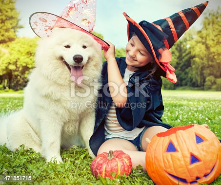 Little girl dressed up for Halloween sitting outdoors with her dog