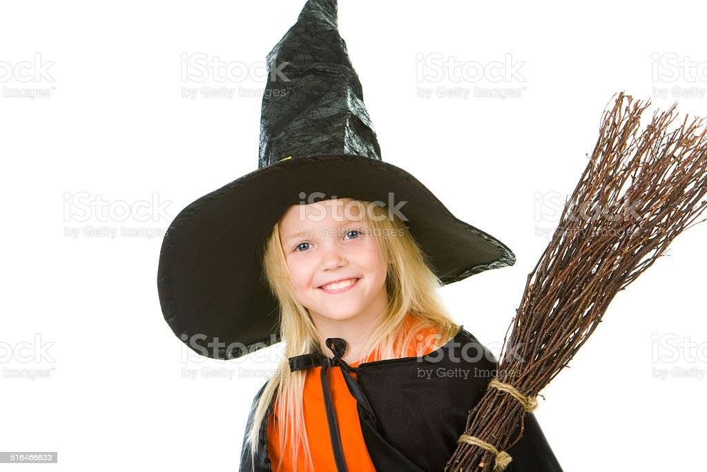 Photo of girl in halloween costume and broom smilling at camera
