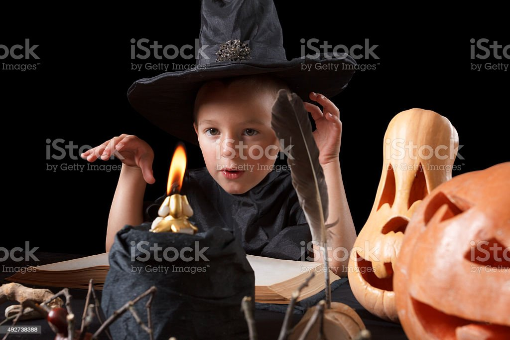 Halloween. Child,  pumpkin and magical things  on black background stock photo