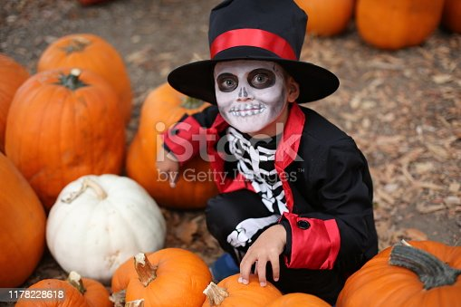 Halloween children playing Trick or Treat. Boy in a Halloween costume of skeleton with hat and smocking between orange pumpkins. Halloween kids