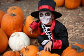 istock Halloween children playing Trick or Treat. Boy in a Halloween costume of skeleton with hat and smocking between orange pumpkins. Halloween kids 1178228618