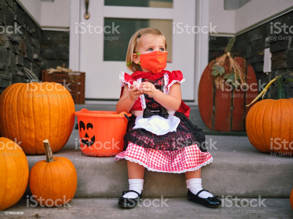 Halloween Children Trick or Treating Wearing Facemasks Children trick or treating on Halloween wearing facemarks for protection. 2-3 Years Stock Photo
