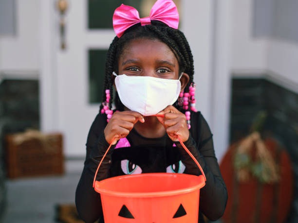 Halloween Children Trick or Treating Wearing Facemasks Children trick or treating on Halloween wearing facemarks for protection. halloween covid stock pictures, royalty-free photos & images
