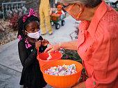 ハロウィーンの子供たちは、フェイスマスクを着用してトリックまたは治療
