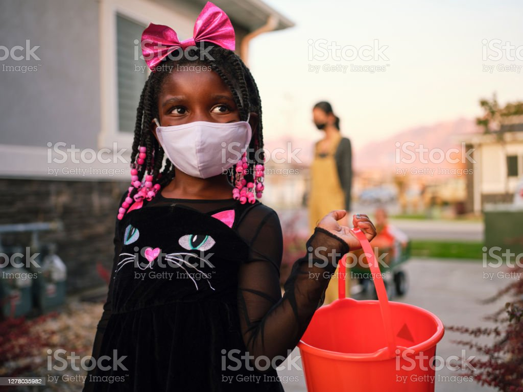 Halloween Children Trick or Treating Wearing Facemasks Children trick or treating on Halloween wearing facemarks for protection. 30-34 Years Stock Photo
