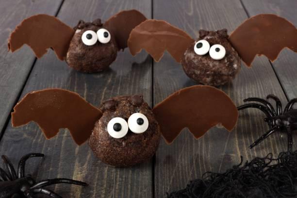 halloween schokolade donut loch fledermäuse gegen dunkles holz - hausgemachte gebackene donuts stock-fotos und bilder