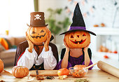 istock Halloween concept.   couple of people dressed as witches and vampires with pumpkins for heads 1173721999