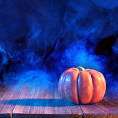 Halloween concept - Orange pumpkin lantern on a dark wooden table with double colored smoke around the background, trick or treat, close up.