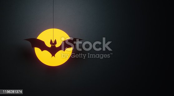 Cut out black bat flying over moon on black background Horizontal composition with copy space. Halloween concept.
