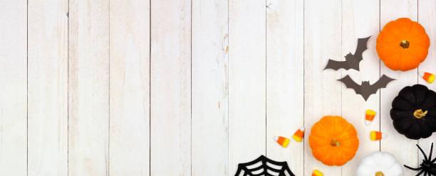 beyaz ahşap üzerinde siyah, turuncu ve beyaz dekor ve şeker ile halloween köşe sınırı - halloween background stok fotoğraflar ve resimler