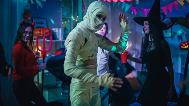 Halloween Costume Party: Old Skinny and Bandaged Mummy Dances. In the Background Zombie, Death, Witch and She Devil Have Fun in a Monster Party Decorated Room Halloween Costume Party: Old Skinny and Bandaged Mummy Dances. In the Background Zombie, Death, Witch and She Devil Have Fun in a Monster Party Decorated Room costume stock pictures, royalty-free photos & images