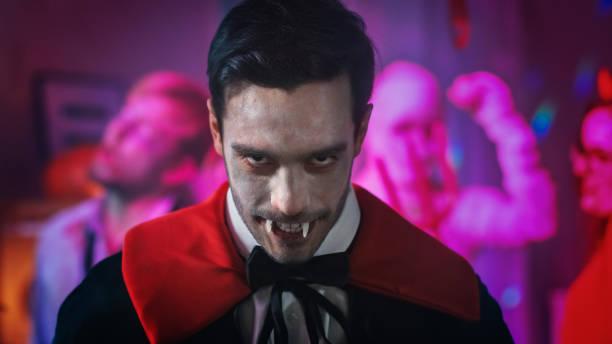halloween kostümparty: porträt von graf dracula smiling creepily, zeigt seine tödlichen blutungen. im hintergrund neon lit, dekorationsraum mit gruselige monster - graf dracula stock-fotos und bilder