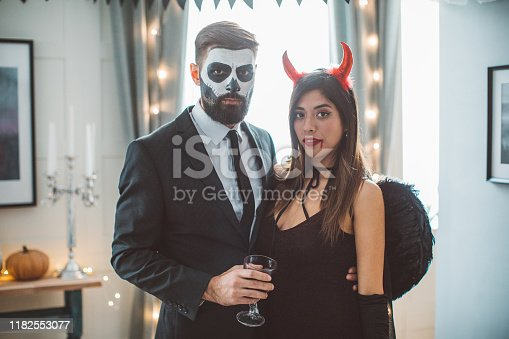 Young couple at home party celebrating Halloween in costume of skeleton and devil, they holding glasses of wine