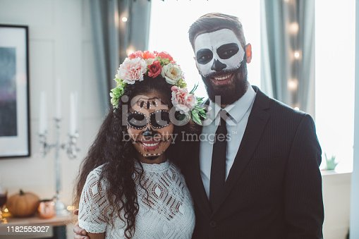 Portrait of young woman with Sugar skull creative make-up and man with make-up costume of skeleton in suit, ready for Halloween party
