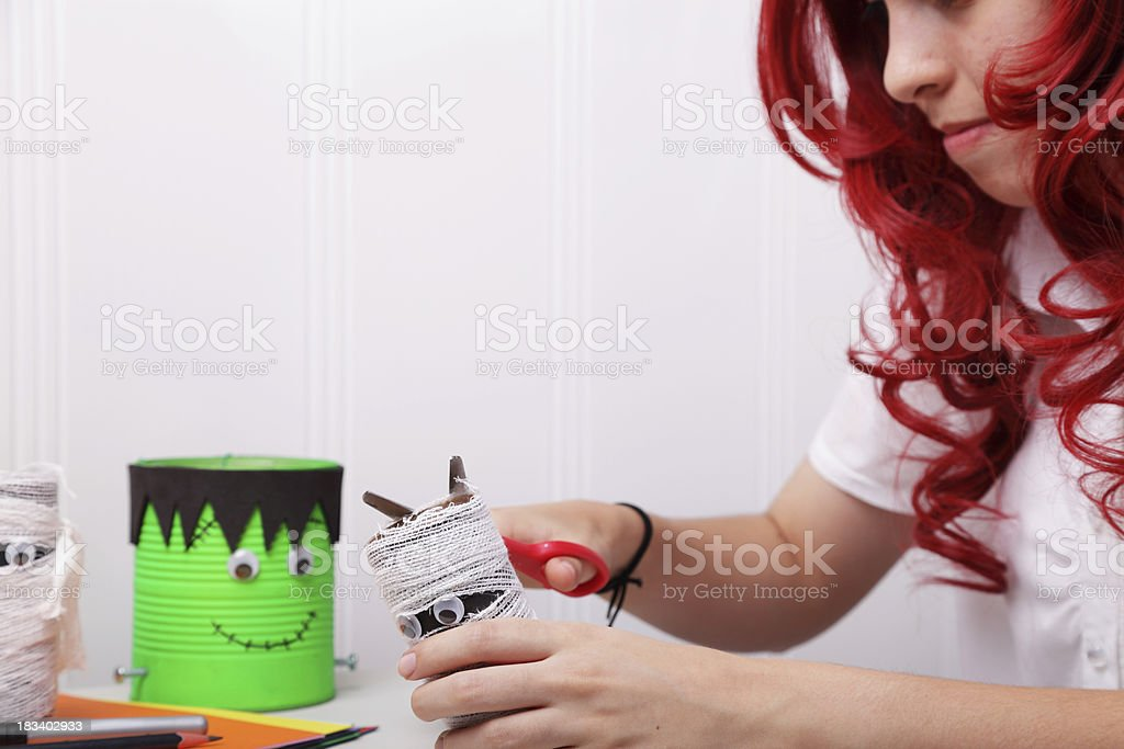 Beautiful red hair girl working on a Halloween craft project.