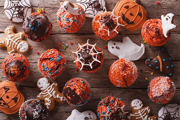 Halloween cupcakes and gingerbread cookies. horizontal top view stock photo