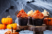 istock Halloween cupcakes and pumpkins on dark web background. Sweets for holiday party. 1180973683