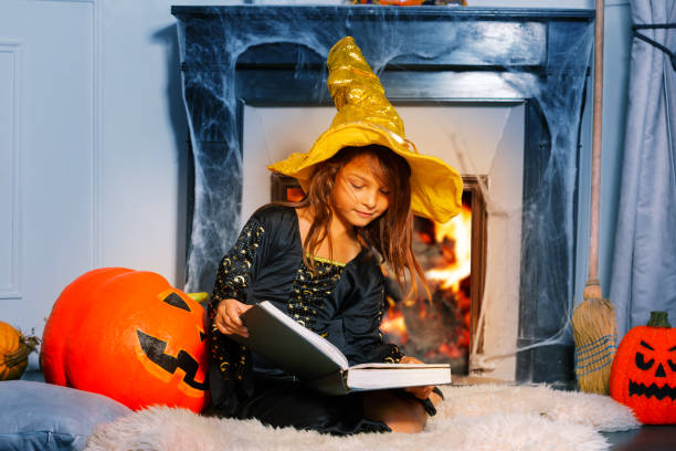 Halloween cute girl with magic book sit by pumpkin stock photo