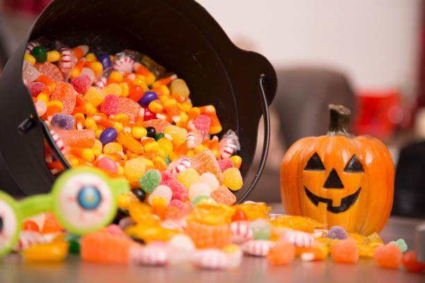 halloween decor, candy at home setting. - halloween candy стоковые фото и изображения