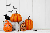 Halloween display with jack o lantern decor and pumpkins against a rustic white wood background. Copy space.