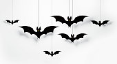 Cut out black bats flying on white background Horizontal composition with copy space. Halloween concept.