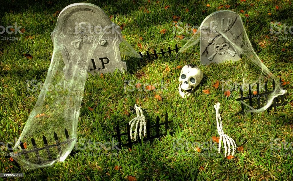 Halloween Decorations of a Skeleton with a Spider on Its Head Climbing Out of a Grave stock photo