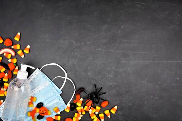 halloween durante el borde de la esquina del coronavirus con caramelos, máscara facial y desinfectante de manos sobre un fondo negro - halloween covid fotografías e imágenes de stock