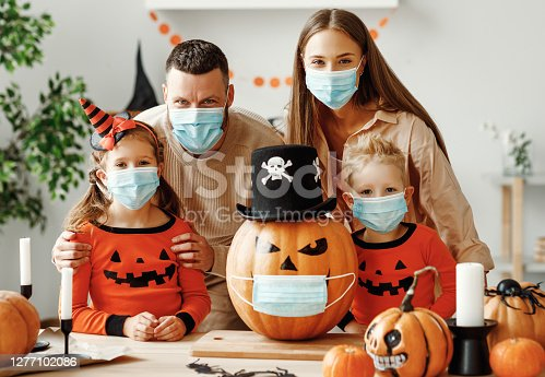 Cheerful family  in medical masks makes jack o lantern out of a pumpkin and  decorates house  in cozy kitchen during Halloween celebration at home during the covid19 coronavirus pandemic