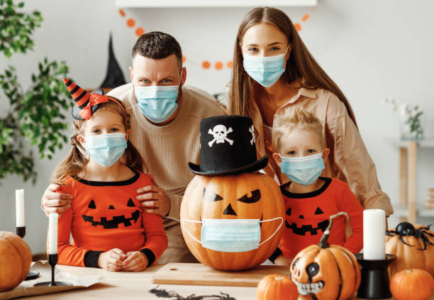 Halloween during the covid19 coronavirus pandemic Cheerful family  in medical masks makes jack o lantern out of a pumpkin and  decorates house  in cozy kitchen during Halloween celebration at home during the covid19 coronavirus pandemic halloween covid stock pictures, royalty-free photos & images