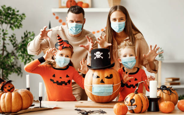 Halloween during the covid19 coronavirus pandemic Cheerful family  in medical masks  makes jack o lantern   out of a pumpkin and  scare for camera  in cozy kitchen during Halloween celebration at home during the covid19 coronavirus pandemic halloween covid stock pictures, royalty-free photos & images