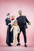 Halloween Family. Happy Father, Mother and Children Girls in Halloween Costume and Makeup. Bloody theme: the crazy maniak faces on pink studio background