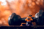 Halloween festival Close up of Halloween head Pumpkins doll and the black iron dumbbell. Fitness, healthy active lifestyle on Halloweeen day concept.