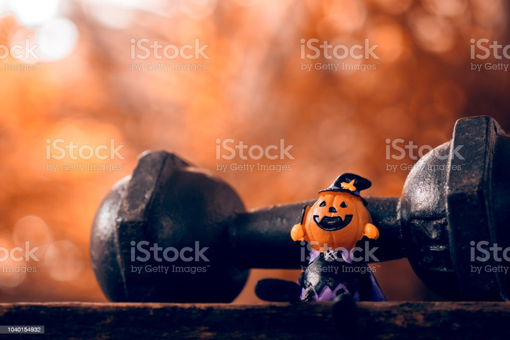 Halloween festival Close up of Halloween head Pumpkins doll and the black iron dumbbell. Fitness, healthy active lifestyle on Halloweeen day concept. stock photo