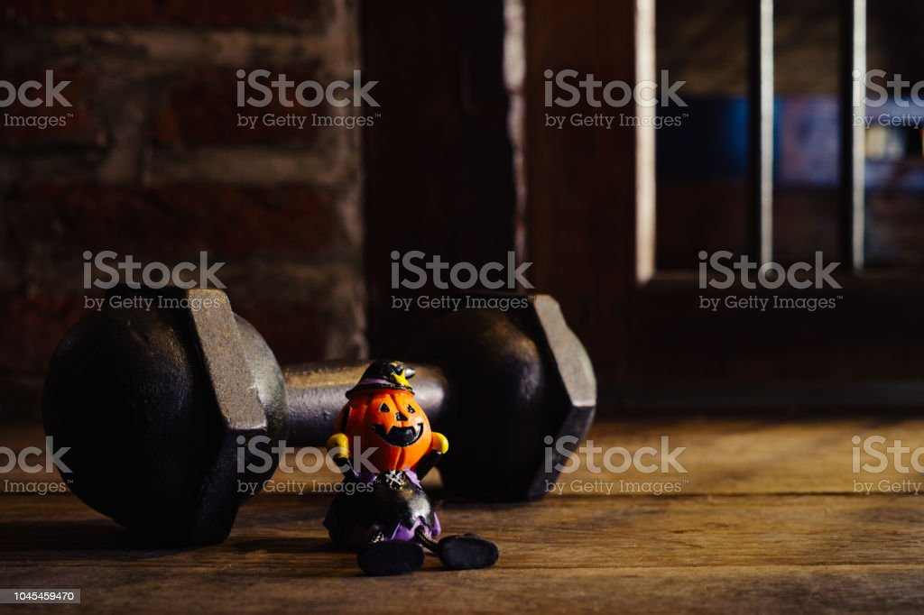 Halloween festival Close up of Head Doll Pumpkins haunted spooky and the black iron dumbbell. Fitness, healthy active lifestyle on Halloweeen day concept. stock photo