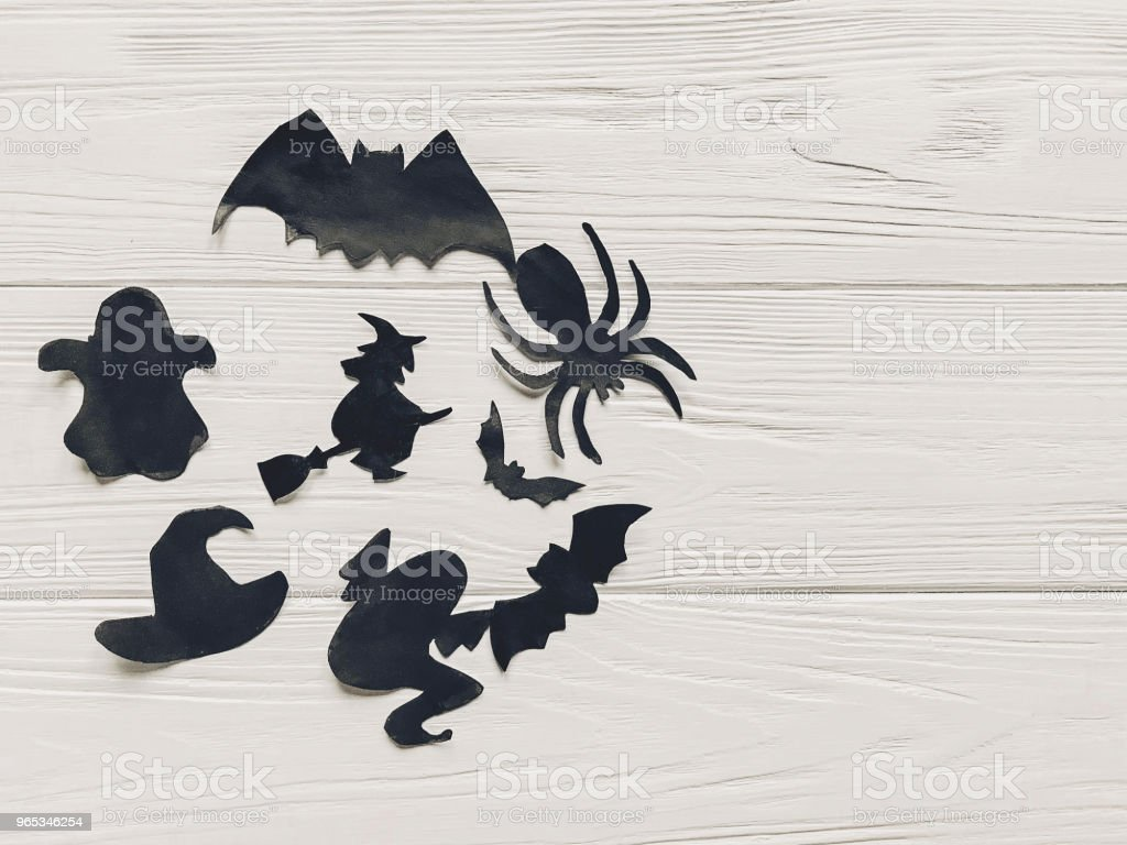 halloween flat lay. happy halloween concept, space for text. witch ghost bats and spider black decorations on white wooden background top view. simple cutouts for  holiday celebration. seasonal greetings royalty-free stock photo
