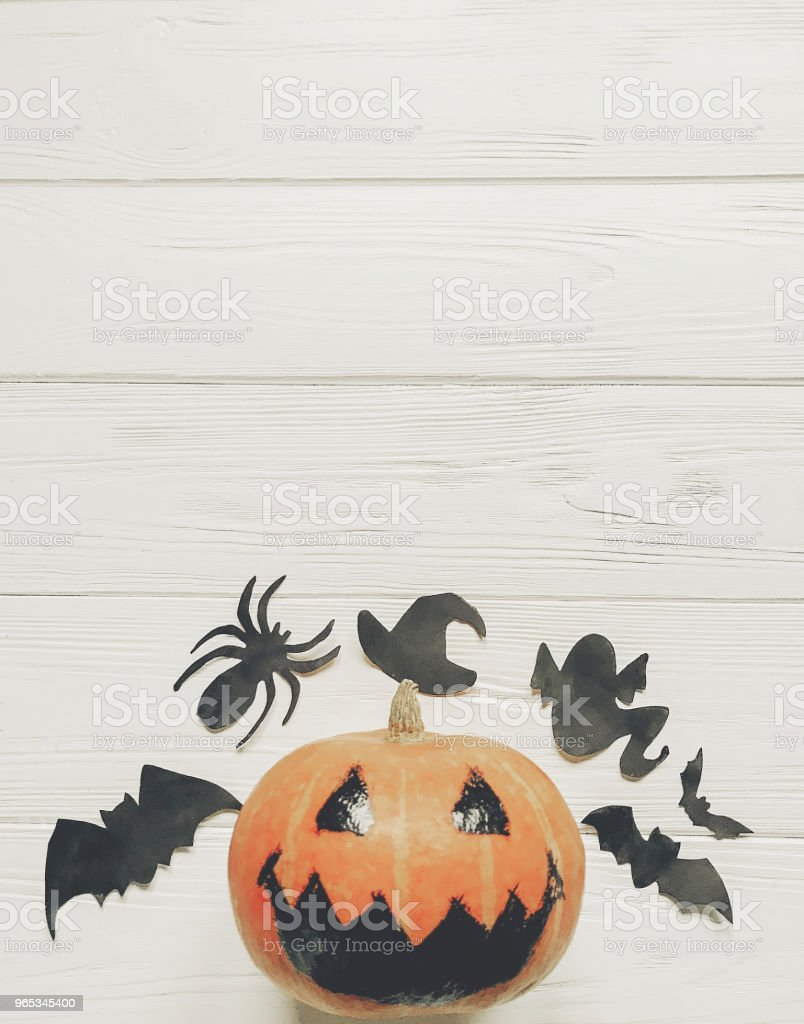 halloween flat lay. jack lantern pumpkin with witch ghost bats and spider black decorations on white wooden background top view, space for text. seasonal greetings. happy halloween concept zbiór zdjęć royalty-free