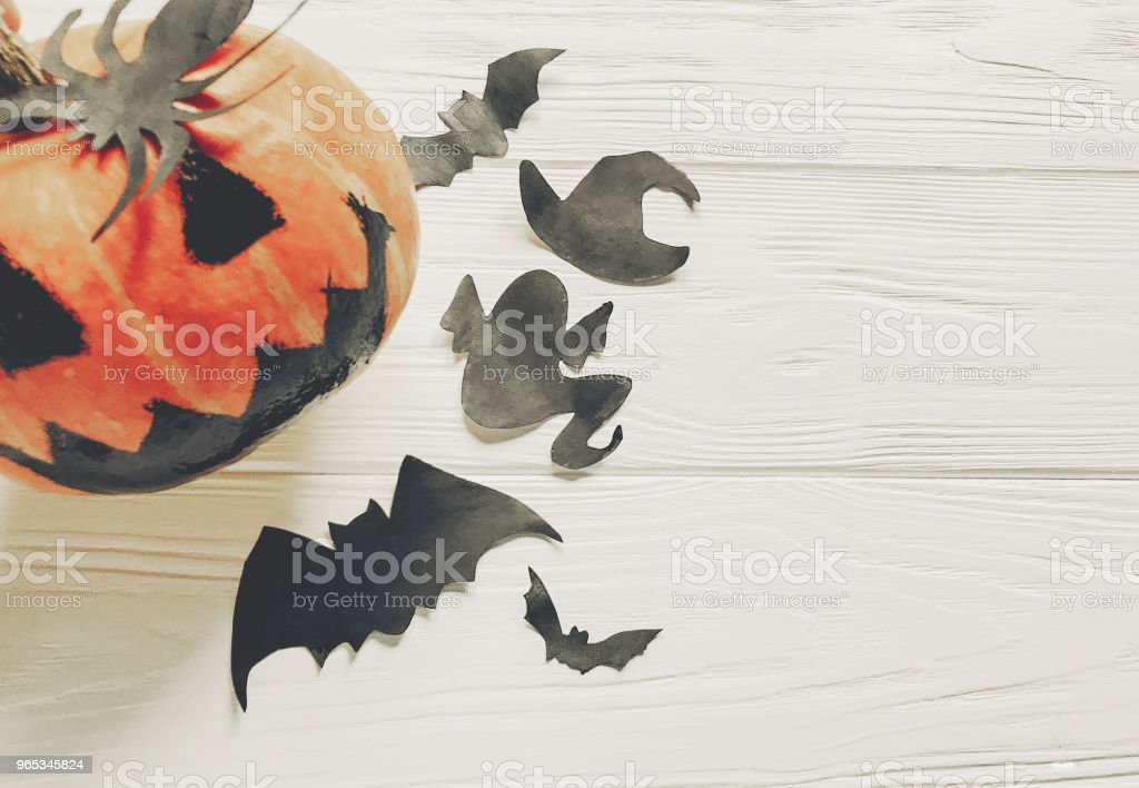 halloween flat lay. jack lantern pumpkin with witch ghost bats and spider black decorations on white wooden background top view, space for text. seasonal greetings. happy halloween concept royalty-free stock photo