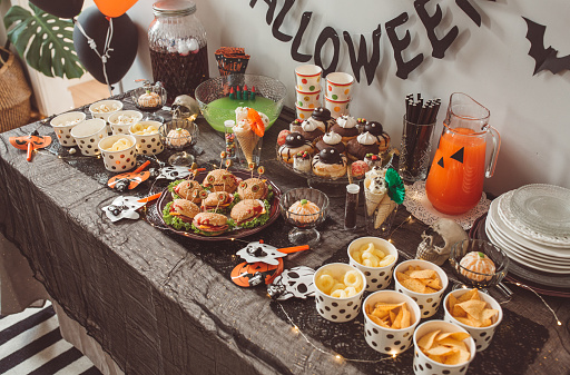 Food table filled with different type of food and drinks ready for Halloween party