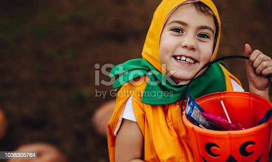 Close up portrait of cute little girl in Halloween costume holding pumpkin bucket outdoors at the park. Little girl child out for trick or treating on Halloween.