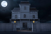 A Halloween haunted house / mansion at night with a full moon and bats.