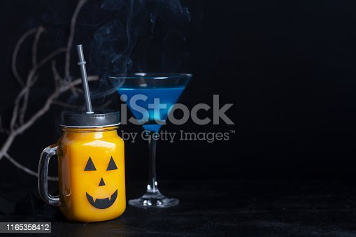 Halloween healthy pumpkin or carrot drinks in the glass jar, artificial eyeballs in a blue liquid on a black background with copy space