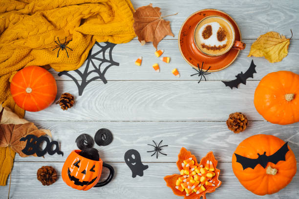 Halloween holiday background with coffee cup, pumpkin and autumn leaves on wooden table. stock photo