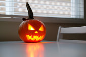 istock Halloween holiday celebration symbol, pumpkin on kitchen table glowing 1169499528