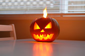 istock Halloween holiday celebration symbol, pumpkin on kitchen table glowing 1169499535